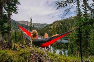 Woman relaxing in hammock overlooking lake