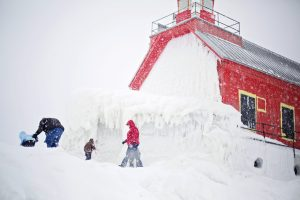 Active family in the snow by lighthouse
